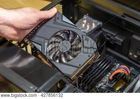Installing A Video Card On The Motherboard. The Technician Installs Computer Components In A Open Pc