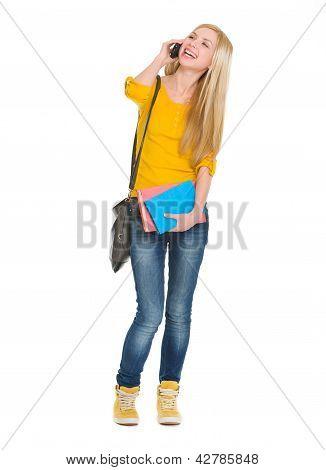 Full Length Portrait Of Smiling Student Girl Talking Mobile Phon