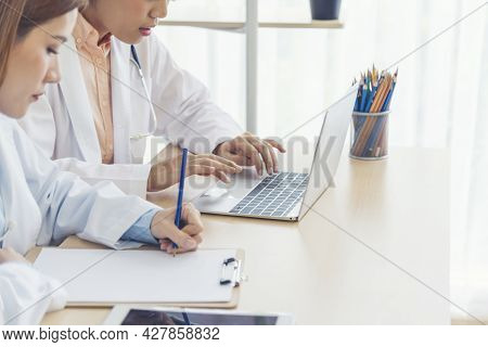 Two Asian Women Doctors Discuss Meeting Doctor's Office Medical Clinic Using Laptop Consulting Patie