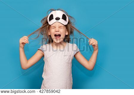 Spoiled Little Girl In Sleeping Mask, Tearing Her Hair Isolated On Blue Background. Stressed Kid. Sc