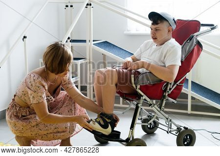 Mother Helping Disabled Boy 17 Years Old In Wheelchair With Cerebral Palsy To Put On Shoes, Before G