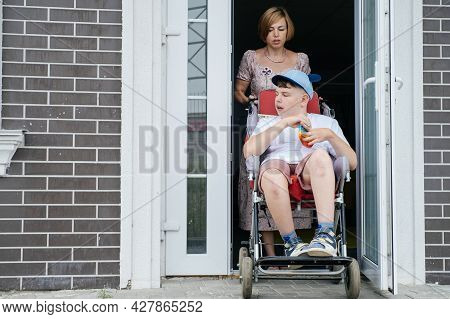 Mother With Disabled Teenage Child In Big Stroller. Accessibility Of People In Wheelchairs. Woman Go