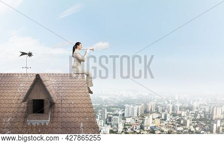 Elegant Young Woman Playing Trumpet On Edge Of Roof. Girl In White Business Suit And Gloves With Mus