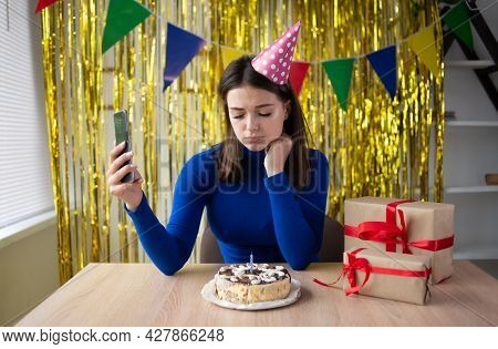 A Sad Young Woman Sits In A Festive Cap Alone At The Table Near A Festive Cake On Her Birthday Holds