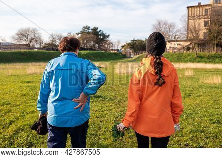 Family Outdoor Vacation. Older Grandmother Walking Down The Park With Her Granddaughter. Rear View.