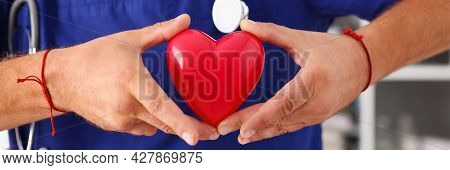 Male Doctor Hold In Arms Red Toy Heart