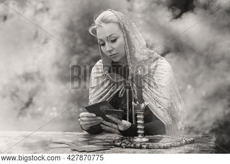 Magical Ritual With A Candle And Spell In Forest. Witchcraft And Esoteric Concept. Wicca Or Paganism