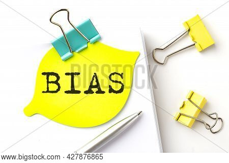 Bias Text On Yellow Sticker On The Notebook With Pen