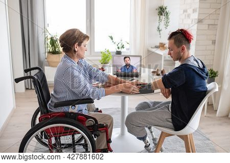 Disabled People Sitting At The Table Indoors At Home, Video Consultation With Doctor.