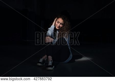 Portrait Of Happy Young Woman Sitting Indoors Against Black Bacground.