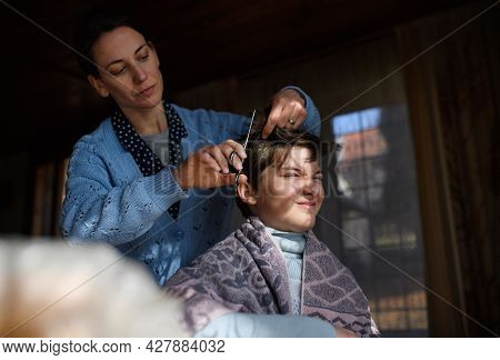 Portrait Of Poor Woman Cutting Daughters Hair Indoors At Home, Poverty Concept.
