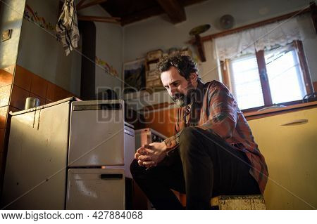 Portrait Of Poor Mature Man Sitting Indoors At Home, Poverty Concept.