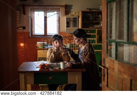 Poor Mature Mother And Sad Small Daughter Learning Indoors At Home, Poverty Concept.
