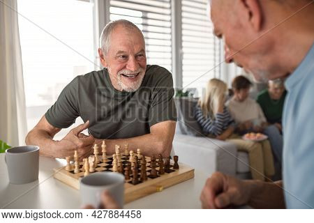 Group Of Senior Friends Playing Board Games Indoors, Party And Social Gathering Concept.