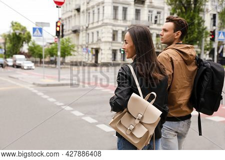 Young Couple Waiting To Cross Street, Back View. Traffic Rules And Regulations