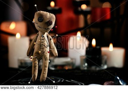 Voodoo Doll Pierced With Pins On Table In Dark Room, Space For Text. Curse Ceremony