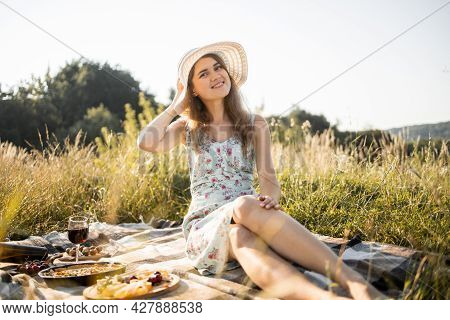 Picnic On The Nature. Portrait Of Beautiful Young Smiling Lady In Dress And Stylish Hat, Sitting On