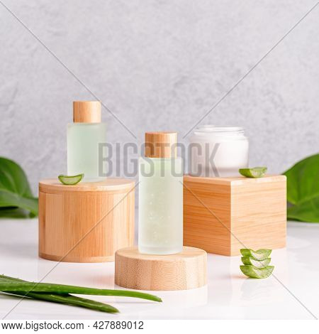 Aloe Vera Face Serum And Cream In Reusable Bottles On Wooden Stands With Aloe Vera Leaves On Concret