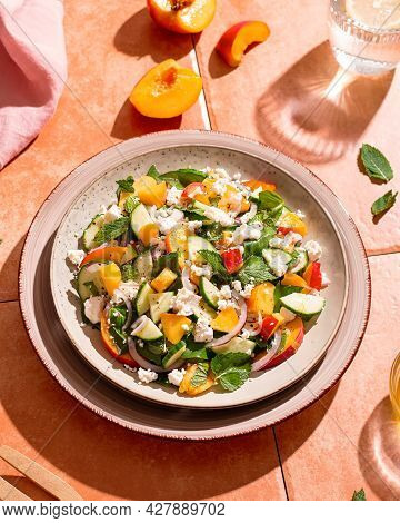 Peach And Cheese Salad With Dressing And Herbs On Terracotta Tile Table In Hard Light With Shadows.
