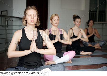 Pretty Young Woman Attending Yoga Class, She Is Meditating In Lotus Position With Hands In Namaste M