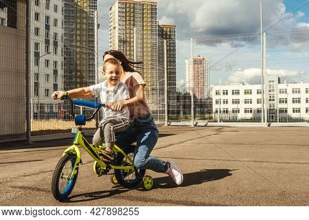 Boy Rides A Bike With His Mother.