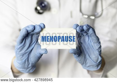 A Medical Worker In Gloves Holds A Card With The Words Menopause. Medical Concept.