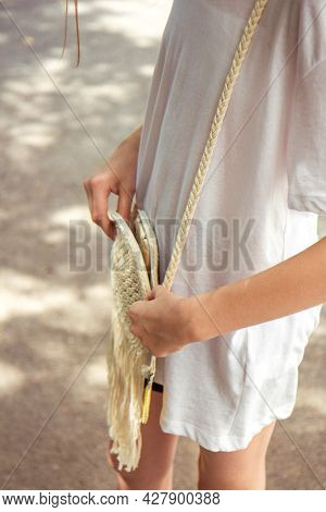 Teenager Girl In Casual Clothes And Wicker Bag Walks In The Park In Summer And Puts Things In Wicker