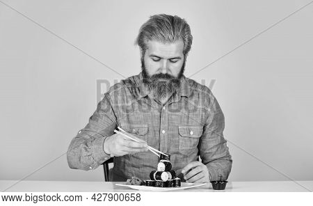 Eastern Culture. Bearded Hipster Eating Rolls. Japanese Food Delivery. Sushi Rolls. Japanese Cuisine