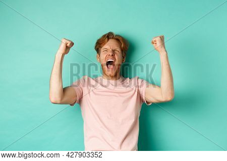 Young Redhead Man Triumphing As Watching Sport Game, Making Bet On Winning Team And Rejoicing, Screa