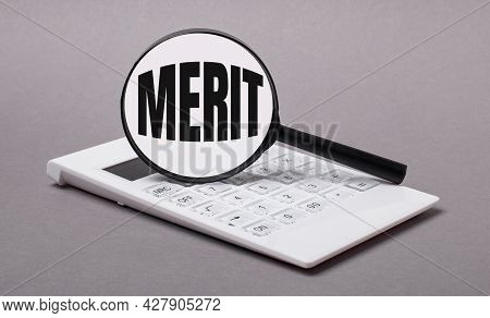 On Gray Background Black Calculator And Magnifier With Text Merit. Business Concept
