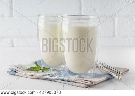 Glasses Of Organic Kefir, Yogurt Or Ayran On White Table Against Brick Wall. Fermented Dairy Milk Pr