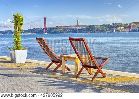 Portugal Travel Ideas. Line Of Wooden Cahris Placed In Front Of 25 April Bridge In Lisbon At Tagus R