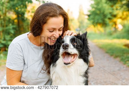 Smiling Young Attractive Woman Playing With Cute Puppy Dog Border Collie On Summer Outdoor Backgroun