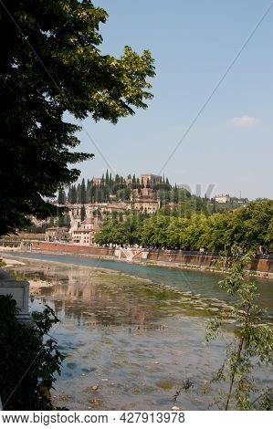 A Scenic Hilltop Town In Tuscany In Italy With The River Flowing In The Foreground Framed By A Tree