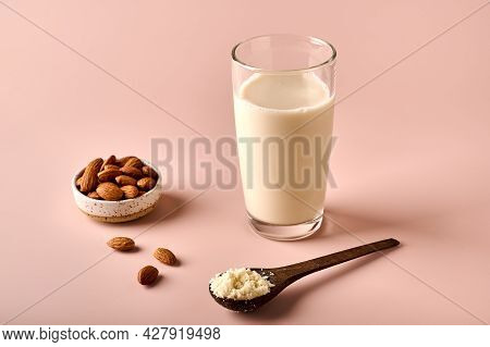 Almond Milk In Glass, Flour In Wooden Brown Spoon And Nut Kernels On Pink Powder Background. Selecti