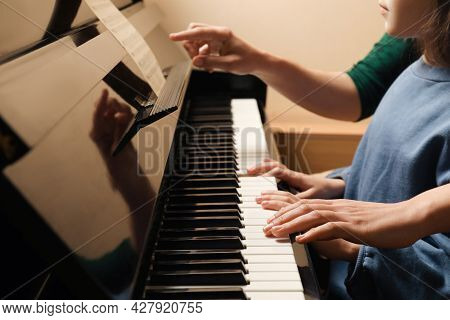 Young Woman With Child Playing Piano, Closeup. Music Lesson