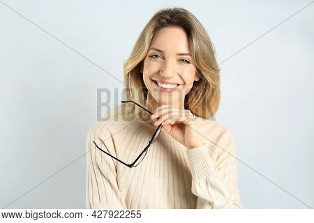 Portrait Of Happy Young Woman With Beautiful Blonde Hair And Charming Smile On Light Background