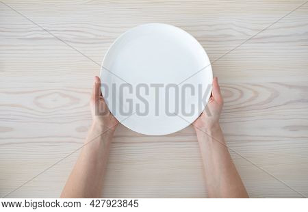 Woman Holding Empty Plate Waiting For Food, Sitting On Wooden Table, Top View, Copy Space