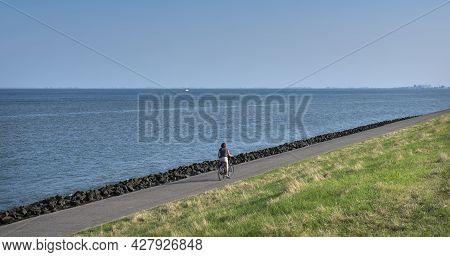 Oudeschild, Netherlands, 19 July 2021: Woman Rides Bicycle On Dike Of Wadden Sea On Dutch Island Of