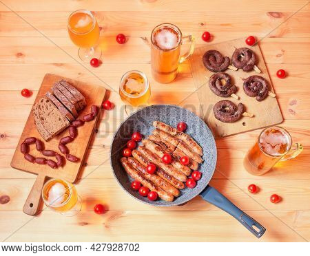 Frying Pan With Roasted Sausages, Roasted Sausages On Cutting Board, Beer Mugs, Beer Glasses, Bread