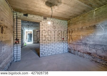 Empty Unfurnished Basement Room With Minimal Preparatory Repairs. Interior With White Brick Walls