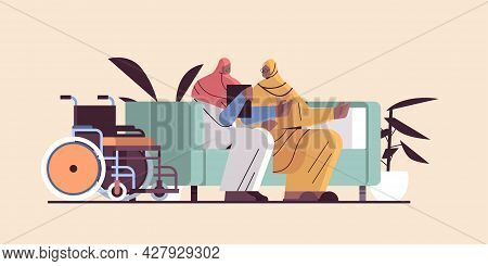 Friendly Nurse Or Volunteer Supporting Arab Elderly Woman Home Care Services Healthcare And Social S