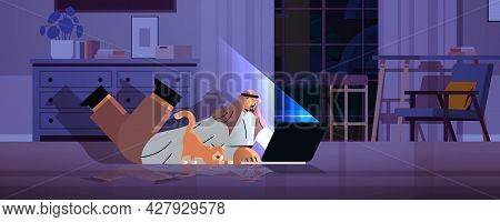 Overworked Arab Businessman Freelancer Looking At Laptop Screen Arabic Man With Dog Lying On Floor I