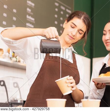 Beautiful Caucasian Barista Women Fill White Milk Into Takeaway Hot Coffee Cup At Coffee Bar In Cafe