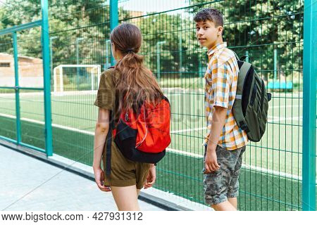 two teenagers boy and girl on the way to the school, education and back to school concept