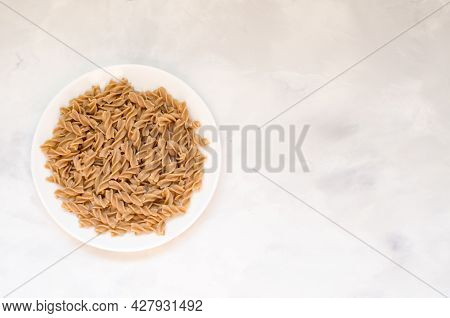 Organic Buckwheat Fusilli Pasta In A White Plate. Gluten Free Whole Grain Noodles. Healthy Food Conc