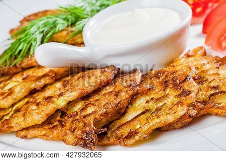 Zucchini Fritters With Sour Cream, Tomato And Dill On A White Plate