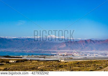 Spanish Landscape. Sea Coast With Many Plastic Greenhouses In Almeria Region And Sierra Nevada Mount