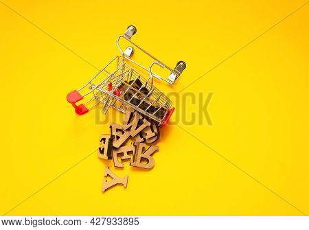 Scattered Wooden Letters Of The English Alphabet From A Miniature Shopping Trolley On A Yellow Backg