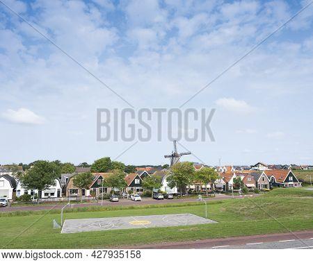 Dutch Village With Windmill Of Oudeschild On Dutch Island Of Texel Seen From Ijsselmeer Dike In Summ